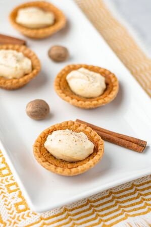 Sweet butter tartlet close-up. Mini sugar pies (or butter tarts) with a crisp pastry crust, a sweet filling and pumpkin spice whipped cream on top. A tasty dessert for fall holidays like halloween! Stok Fotoğraf