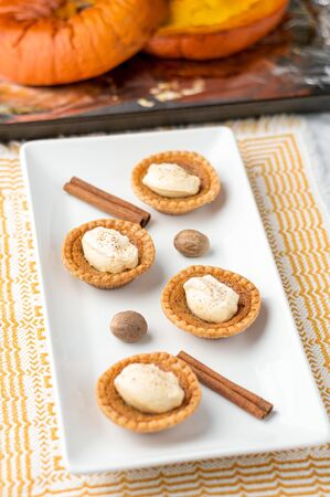 Sugary butter tart treats. Mini sugar pies (or butter tarts) with a crisp pastry crust, a sweet filling and pumpkin spice whipped cream on top. A tasty dessert for fall holidays like halloween!