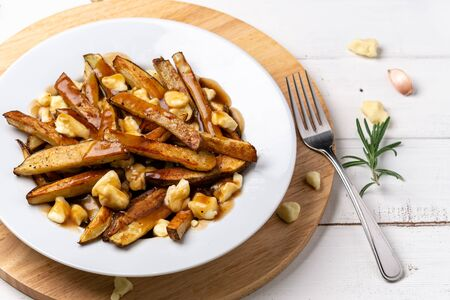 Poutine comfort food closeup. A classic fast food cuisine dish from Quebec. This canadian comfort food is made with french fries mixed with tasty cheese curds and a delicious brown gravy sauce.
