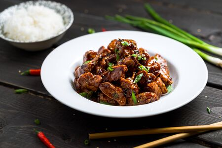 General Tso's Chicken dish low angle view. General Tso's chicken (also tsao or tao) is a popular chinese restaurant food with deep-fried crispy chicken covered in a tasty sweet and spicy sauce.