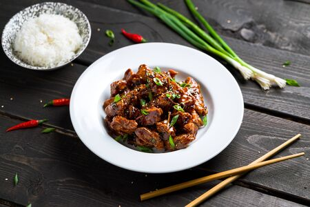 General Tso Chicken plate on dark background. General Tso's chicken (also tsao or tao) is a popular chinese restaurant food with deep-fried crispy chicken covered in a tasty sweet and spicy sauce. Imagens