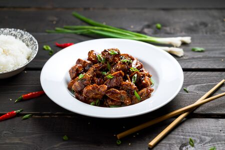 Delicious General Tso's Chicken dish angled view. General Tso's chicken (also tsao or tao) is a popular chinese restaurant food with deep-fried crispy chicken covered in a tasty sweet and spicy sauce. Imagens