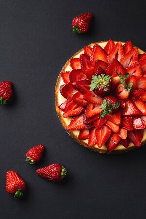 Strawberry Cheesecake overhead portrait view. A classic decadent dessert, this sweet and delicious homemade baked cheesecake is topped with fresh strawberry slices. The perfect cake for a birthday.