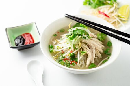 Vietnamese chicken pho noodle soup bowl. A classic authentic vietnamese food, this pho soup is served in a white bowl with chicken broth and lots of fresh garnishes such as cilantro and bean sprouts.