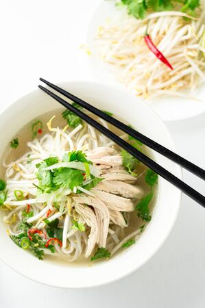 Vietnamese pho soup top view from above. A classic authentic vietnamese food, this pho soup is served in a white bowl with chicken broth and lots of fresh garnishes such as cilantro and bean sprouts.