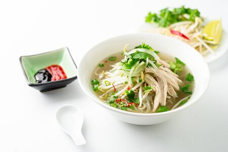Vietnamese pho soup on white background. A classic authentic vietnamese food, this pho soup is served in a white bowl with chicken broth and lots of fresh garnishes such as cilantro and bean sprouts. Imagens