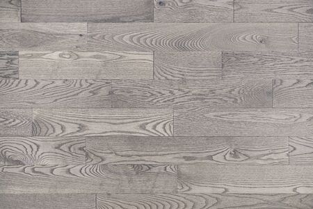 Grey white wood floor texture background viewed from above. Neutral whitewashed hardwood stain gives these wide wooden flooring planks a modern look while the visible wood grain gives a rustic feel.