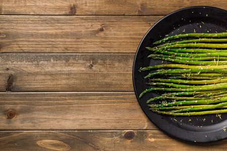 Asparagus on wooden background. Eating healthy food is easy with this homemade vegan dish; roasted asparagus with lemon zest on top. The veggies are served on black plate with wooden table background. Imagens