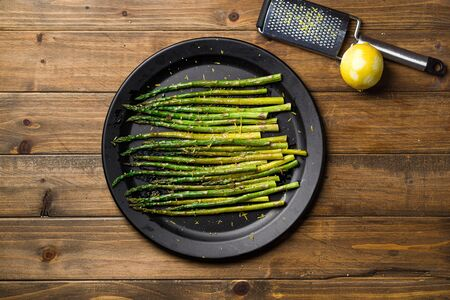 Asparagus plate above top view. Eating healthy food is easy with this homemade vegan dish; roasted asparagus with lemon zest on top. The veggies are served on black plate with wooden table background. Imagens