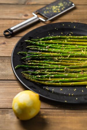 Healthy food lemon asparagus. Eating healthy food is easy with this homemade vegan dish; roasted asparagus with lemon zest on top. The veggies are served on black plate with wooden table background. Imagens
