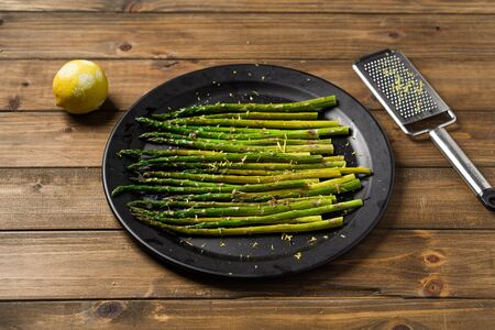Lemon zest asparagus on plate. Eating healthy food is easy with this homemade vegan dish; roasted asparagus with lemon zest on top. The veggies are served on black plate with wooden table background.