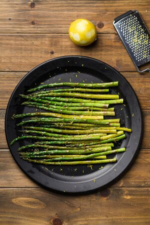 Cooked asparagus from above. Eating healthy food is easy with this homemade vegan dish; roasted asparagus with lemon zest on top. The veggies are served on black plate with wooden table background. Imagens