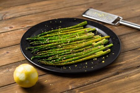 Vegetarian roasted asparagus. Eating healthy food is easy with this homemade vegan dish; roasted asparagus with lemon zest on top. The veggies are served on black plate with wooden table background. Imagens