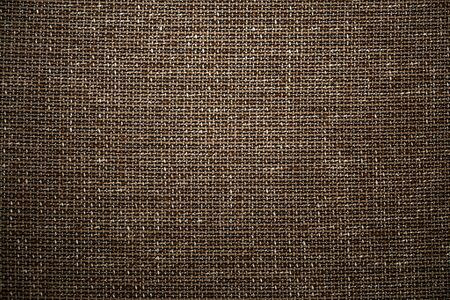 Brown textile fabric background. High resolution close up of brown fabric cloth made of various textile threads. This top view dark fabric background can be used as design element such as backdrop.