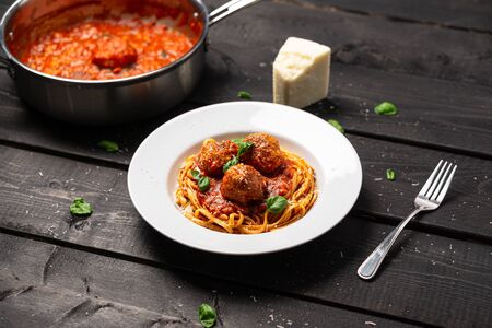 Spaghetti dinner with meatball sauce. Italian pasta dish served in white plate on black wooden background. Spaghetti and meatballs is like bolognese sauce with balls of meat cooked in tomato sauce. Imagens