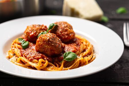 Spaghetti and meatballs plate close-up. Italian pasta dish served in white plate on black wooden background. Spaghetti and meatballs is like bolognese sauce with balls of meat cooked in tomato sauce.