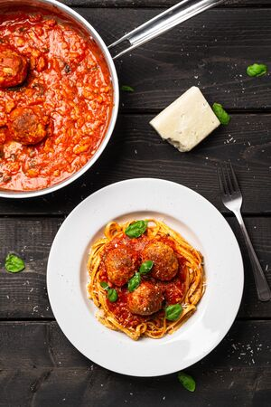 Spaghetti pasta sauce view from above. Italian pasta dish served in white plate on black wooden background. Spaghetti and meatballs is like bolognese sauce with balls of meat cooked in tomato sauce.