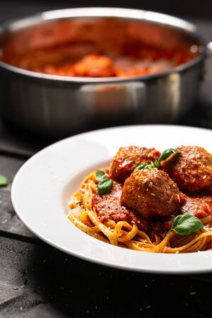 Spaghetti meatball portrait side view. Italian pasta dish served in white plate on black wooden background. Spaghetti and meatballs is like bolognese sauce with balls of meat cooked in tomato sauce. Imagens
