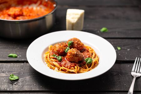 Spaghetti meatball plate stock photo. Italian pasta dish served in white plate on black wooden background. Spaghetti and meatballs is like bolognese sauce with balls of meat cooked in tomato sauce.