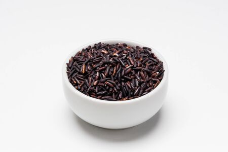 Black rice bowl on white background. Rice comes from seeds of grass, it is the most consumed staple food ingredient. Black rice is a type of glutinous short grain rice often used in asian cuisine.