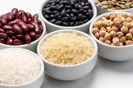 Rice and beans ingredients closeup. Bowl of basmati rice surrounded by other varieties of grains and legumes, such as: chickpeas, red kidney beans, green lentils, black turtle beans and jasmine rice. Imagens