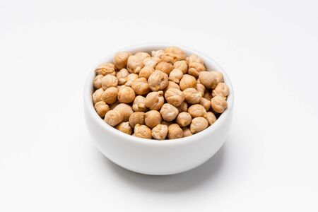 Chickpeas bowl on white background. These uncooked chickpeas are common staple food ingredients. Also called pulses (dry edible seeds of plants), they are part of the legume family.