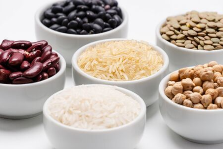 Bowls of mixed legumes and grains. Bowl of basmati rice surrounded by other varieties of grains and legumes, such as: chickpeas, red kidney beans, green lentils, black turtle beans and jasmine rice.