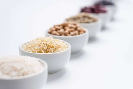 Grains of rice and beans background. Shallow depth of field on basmati rice grains in a white bowl with other types of rice cereals and bean legumes blurred in the background. Horizontal orientation.