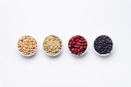 Bean bowls top view white background. These legumes are all pulses (dry edible plant seeds). The following ingredients can be seen: chickpeas, red kidney beans, green lentils and black turtle beans.