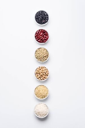 Various legumes and grains top view. Bowls of staple food ingredients like chickpeas, red kidney beans, green lentils, black turtle beans, jasmine rice and basmati rice on white background from above.