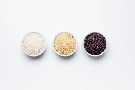 Rice bowls top view white background. 3 varieties of rice, white jasmin, basmati and black rice in white bowls on white background with copy space. Rice is the most consumed staple food ingredient.