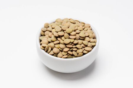 Green lentils bowl on white background. These uncooked green lentils are common staple food ingredients. Also called pulses (dry edible seeds of plants), they are part of the legume family. Imagens