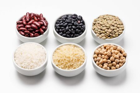 Uncooked rice and beans ingredients. Bowl of basmati rice surrounded by other varieties of grains and legumes such as: chickpeas, red kidney beans, green lentils, black turtle beans and jasmine rice.