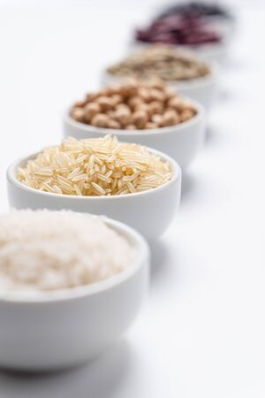 Basmati rice long grain closeup. Shallow depth of field on basmati rice grains in a white bowl with other types of rice cereals and bean legumes blurred in the background. Vertical orientation. Imagens