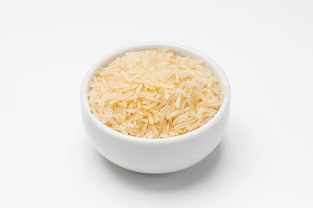 Basmati rice bowl on white background. Rice comes from seeds of grass, it is the most consumed staple food ingredient. Basmati rice is a type of aromatic long grain rice often used in indian cuisine.
