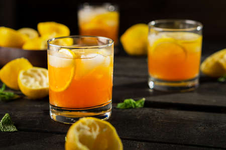 Homemade lemon iced tea glass on dark background. A refreshing summer drink made of fresh hand squeezed lemon mixed with cold black tea, ice and sugar. Add orange juice & alcohol for a cool cocktail. Imagens