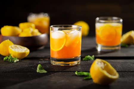 Lemon iced tea drink photo on dark background. A refreshing summer drink made of fresh hand squeezed lemon mixed with cold black tea, ice and sugar. Add orange juice & alcohol for a cool cocktail.