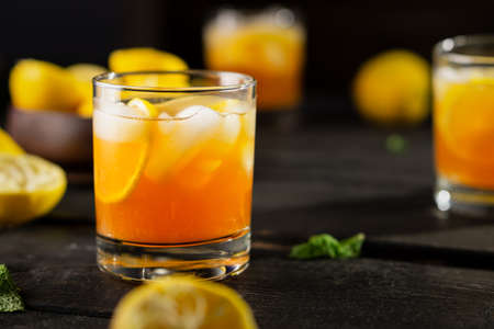 Cold drink of lemon iced tea on dark background. A refreshing summer drink made of fresh hand squeezed lemon mixed with cold black tea, ice and sugar. Add orange juice & alcohol for a cool cocktail. Imagens
