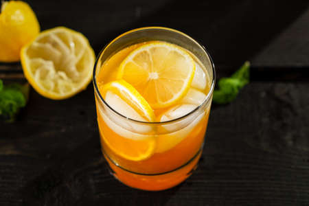 Citrus lemon iced tea close up on dark background. A refreshing summer drink made of fresh hand squeezed lemon mixed with cold black tea, ice and sugar. Add orange juice & alcohol for a cool cocktail. Imagens