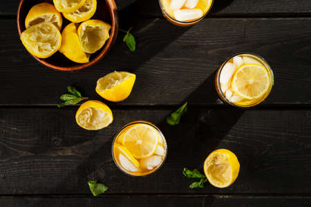 Lemon iced tea from above on dark background. A refreshing summer drink made of fresh hand squeezed lemon mixed with cold black tea, ice and sugar. Add orange juice & alcohol for a cool cocktail. Imagens