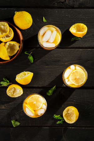 Lemon iced tea top view on dark background. A refreshing summer drink made of fresh hand squeezed lemon mixed with cold black tea, ice and sugar. Add orange juice & alcohol for a cool cocktail. Imagens