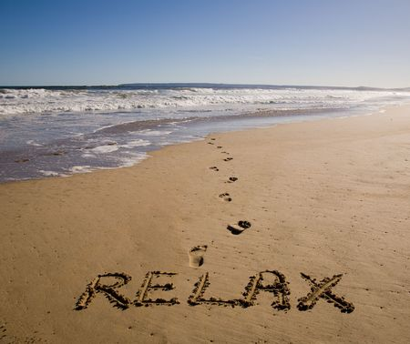 beach scene: Tranquil beach scene with relax written in sand Stock Photo