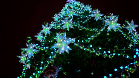 Close up large luminous multi-pointed blue stars and yellow balls decoration on Christmas tree at Christmas market square Outdoor