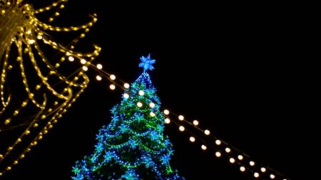 View of Christmas tree decorated large luminous multi-pointed blue stars and yellow balls through garland of yellow lights encircling city square Outdoor Foto de archivo