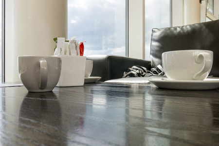 Relaxing cup of coffee with cup and milk jug on coffee shop table photo