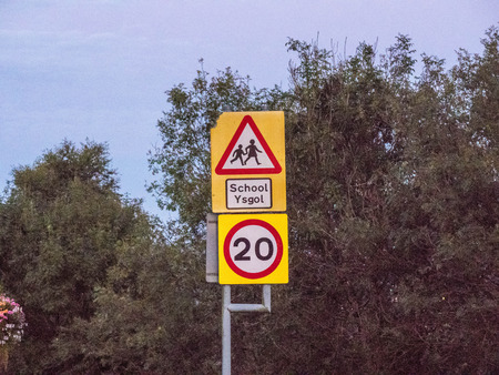 Bilingual road sign near school in Wales warning of children crossing and maximum speed limit
