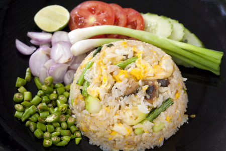 Fried Rice with shrimps serve with herb like green chilly, Red onion, spring onion, and Slice tomato , Slice cucumber, very famous Thai street food  photo