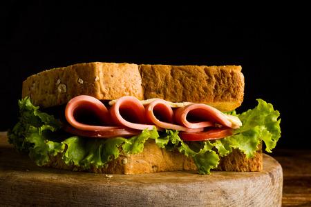 sandwish: Sandwich ham cheese, whole grain bread, organic salad, cheese, fresh tamato and ham Stock Photo