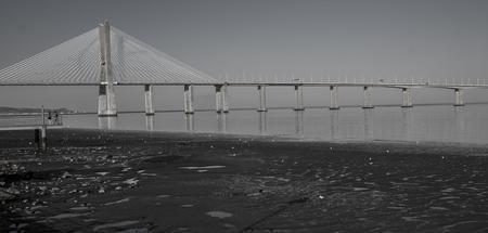 Ebdag in Lissabon onder de Vasco da Gama-brug. Zwart  wit foto's