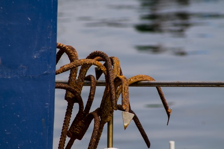rusted sea anchors on a fishing boat moored Archivio Fotografico